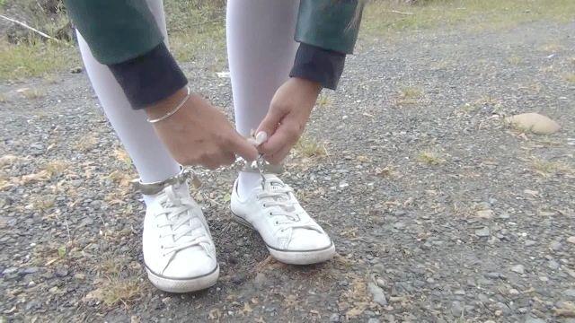 Schülerin weißen Kniestrümpfen und Fußfesseln / Fesseln Handschellen
