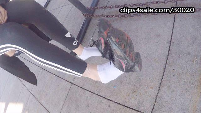 sie spielen mit ihren Schuhen und Socken in der Öffentlichkeit zu machen